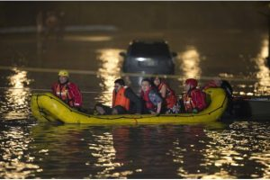 Soaking wet Go Train passengers are rafted to safety during a surprise flash flood in Toronto.